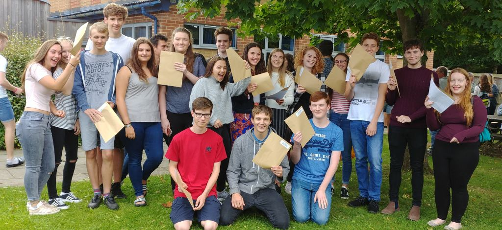 students brandishing their results envelopes